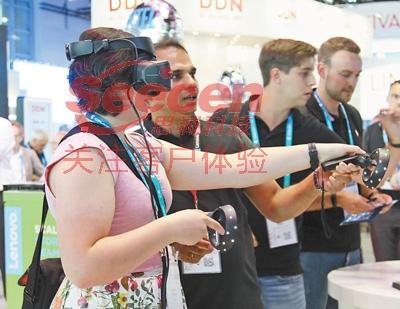 参观者在联想集团展台前体验虚拟现实(VR)设备